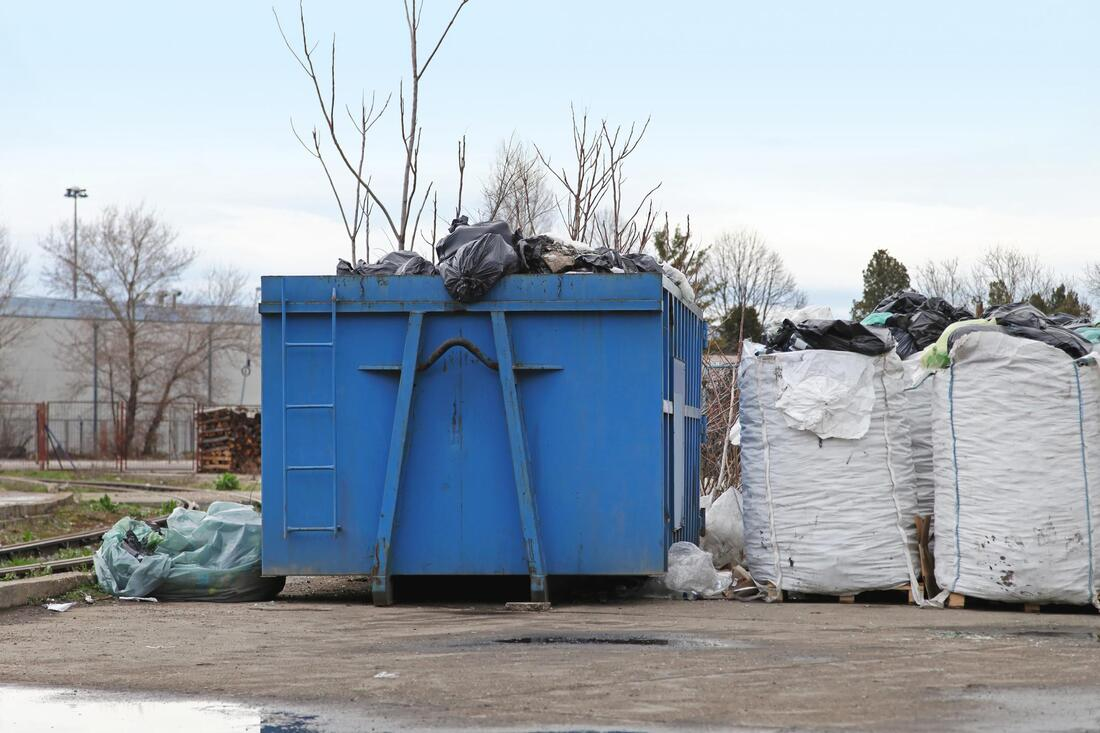 a dump space with blue huge trash container